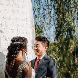 bride and groom in front of custom calligraphy banner